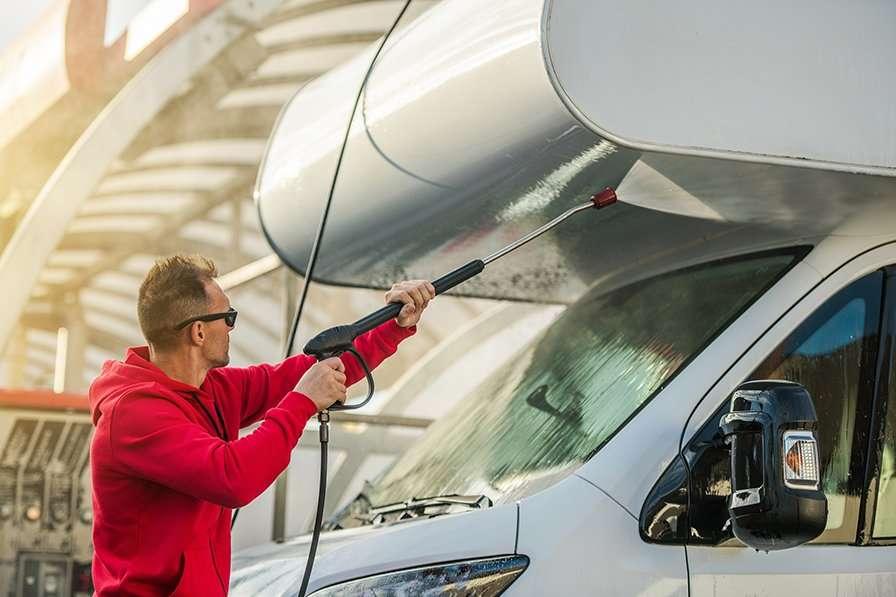 Seasonal RV Recreational Vehicle Motorhome Cleaning Using Pressure Washer. RV Camper Car Washing by Caucasian Men in His 30s.