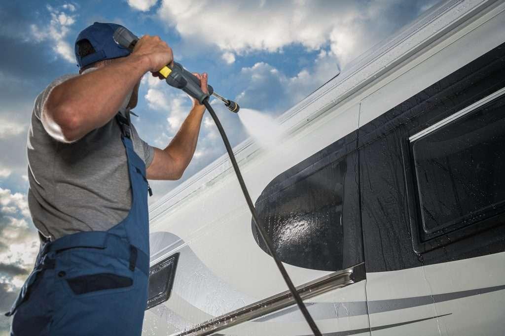 Caucasian Men Pressure Washing His Modern Camper Van RV Class B. Recreational Vehicle Maintenance. Keeping Motorhome Clean.