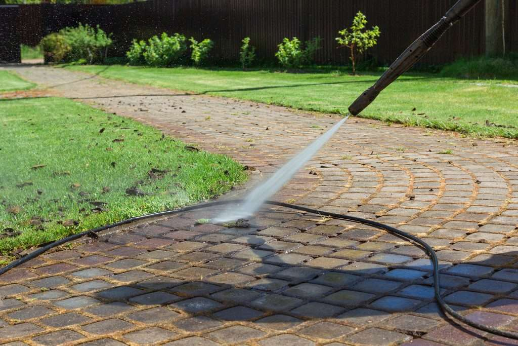 power washingCleaning street with high pressure power washer, washing stone garden paths