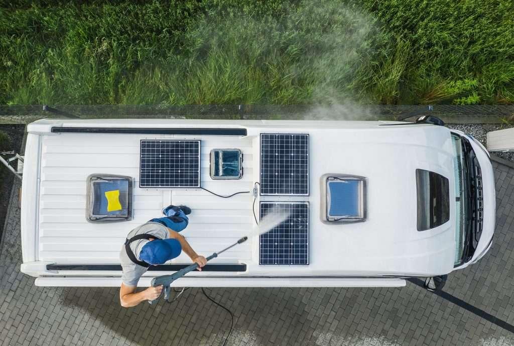 Caucasian Men in His 40s Power Pressure Washing Recreational Vehicle RV Camper Van Roof Equipped with Solar Panels. Camping Pre Season Motorhome Maintenance.